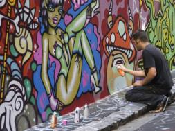 Graffiti artist at work in city laneway.